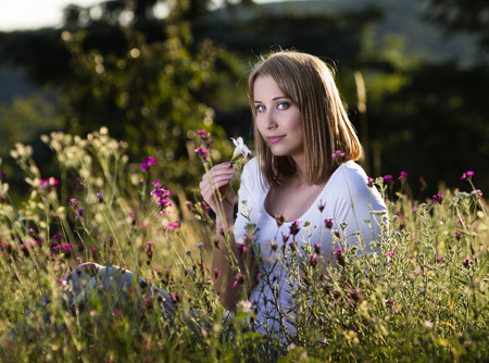 Beautiful young woman in blooming meadow Stock Photo