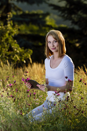 Beautiful young woman with tablet pc in blooming meadow Stock Photo