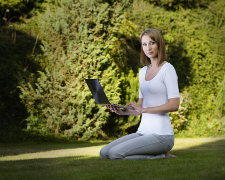 Beautiful young woman sitting with laptop on the grass Stock Photo