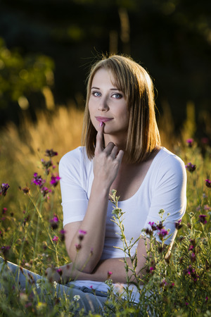 Beautiful thoughtful young woman in blooming meadow
