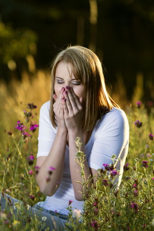 Beautiful young woman in blooming meadow sneezes with allergies