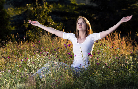 Beautiful young woman taking a breath in blooming meadow Stock Photo