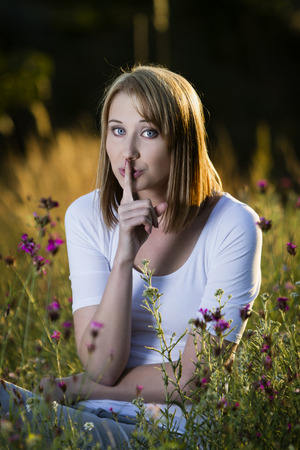 beautiful young blond woman sitting on a flowering meadow showing quiet sign Stock Photo