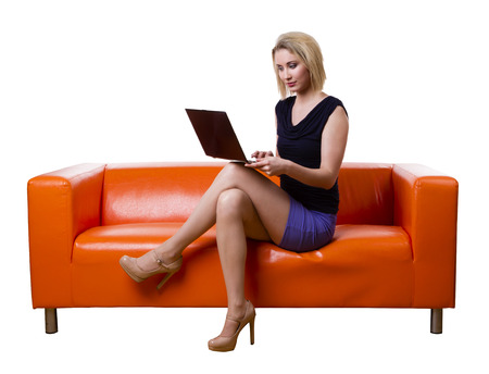 woman sitting with laptop: Young beautiful sexy woman sitting on the couch with a laptop, isolated on white