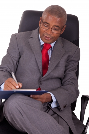 african businessman: african businessman sitting in office chair isolated on white