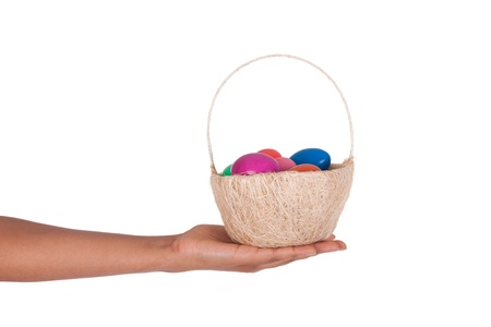 hand basket: Hand holding colorful Easter eggs in the basket