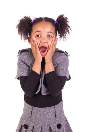 sticking tongue: Muchacha africana joven que pega la lengua hacia fuera, aislado en fondo blanco