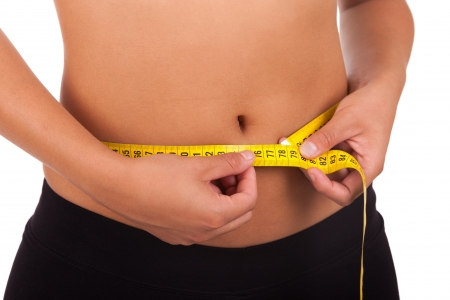 Young african american woman measuring her belly isolated photo