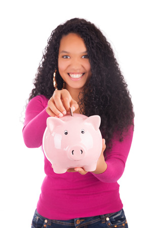 american money: Young african american woman putting coin in piggy bank isolated Stock Photo