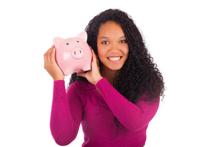 sales bank: Young african american woman putting coin in piggy bank isolated Stock Photo