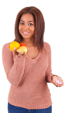 African american girl makes a choice between medicine and fruit Stock Photo - 28032333