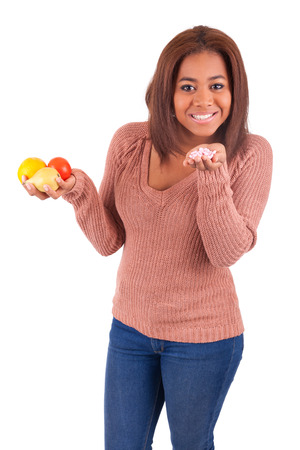 African american girl makes a choice between medicine and fruit Stock Photo - 28032334