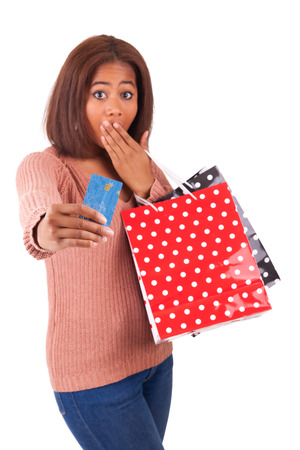 Beautiful african woman smiling holding a credit card and shopping bags photo