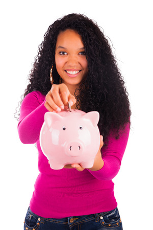 finance girl: Young african american woman putting coin in piggy bank isolated Stock Photo