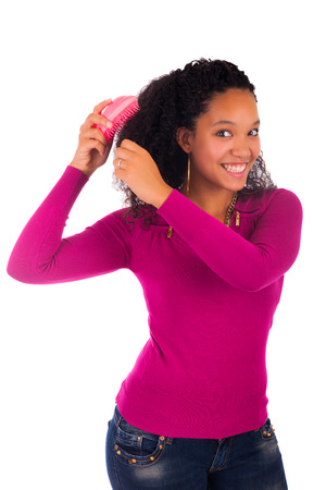 combing hair: Young african american woman combing hair isolated