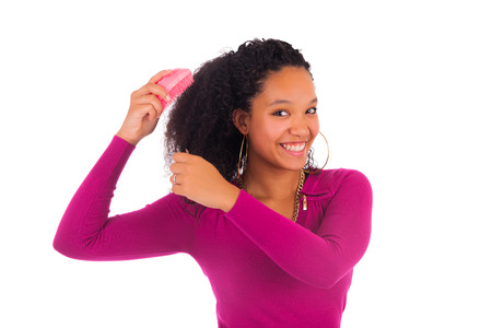 comb: Young african american woman combing hair isolated