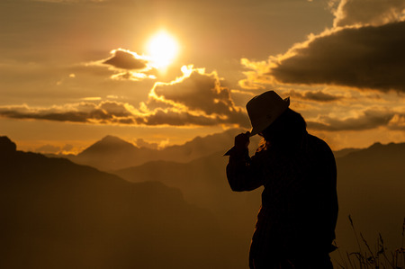 the silhouette of a young girl over the top of tne mountain photo