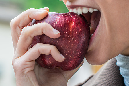 a young actractive girl eats an apple Stock Photo
