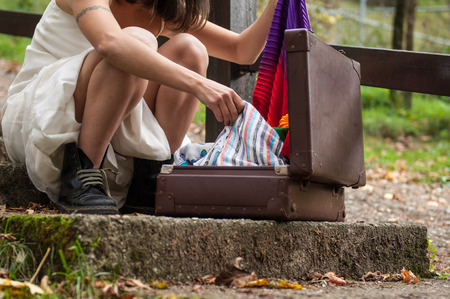 rolling bag: girl looks for the clothes inside her suitcase