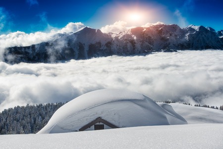 house covered with snow in the high mountains photo