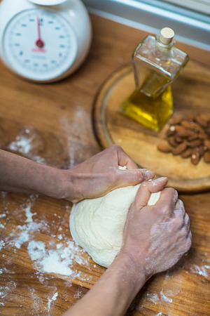 stoking: Knead flour with your hands on the wooden table Stock Photo
