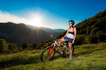 girl in mountain bike during sunset