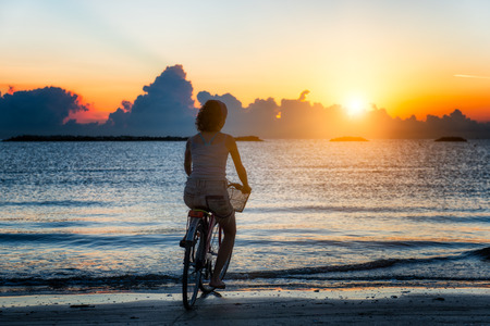 Girl cycling in the sea during sunrise photo