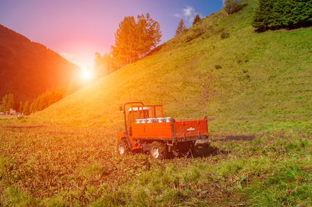 agronomics: tractor in the mountains of Italy during the sunset Stock Photo