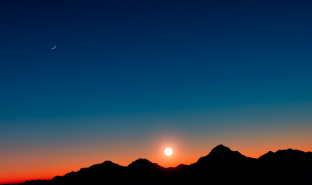 moon  desert: Sunset with mountains in silhouette with the moon Stock Photo