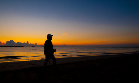 silhouette of a man walking on the sea photo