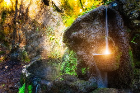 well in the mountain lighted by the sun Stock Photo