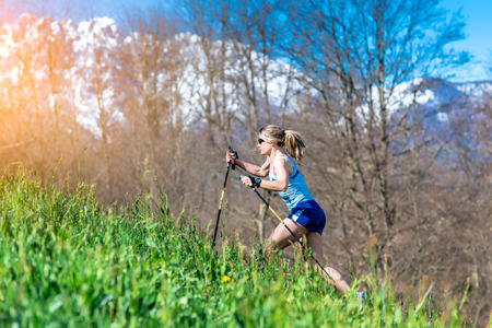 women s health: Girl runs with sticks in the mountains Stock Photo