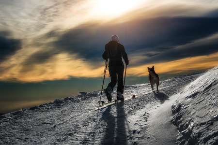 mountaineering: Ski mountaineering silhouette, girl with a dog