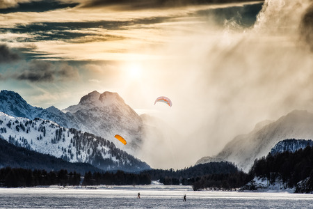 kiting: Two kite surfing on a frozen lake in the high mountains