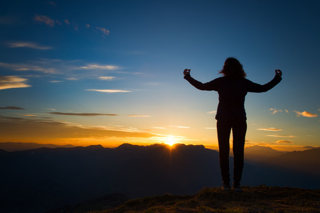 Girl in yoga meditation on top of a mountain at sunset Banco de Imagens