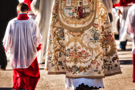 carrying the cross: altar boy and priest During a religious ceremony
