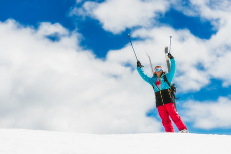 raises: Girl freeride skier, raises his hands before the descent from the top