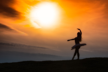 ballerina silhouette: Ballerina silhouette, dancing alone in nature in the mountains at sunset Stock Photo