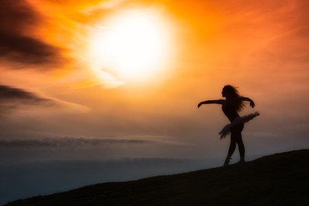 Ballerina silhouette, dancing alone in nature in the mountains at sunset photo
