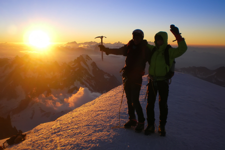 Two climbers on the summit of Mont Blanc at sunrise