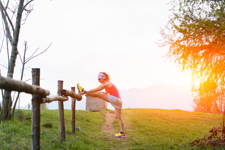 women s health: Girl makes stretching in the nature of a fence