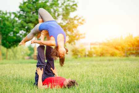 women s health: Couple practicing acroyoga in the park