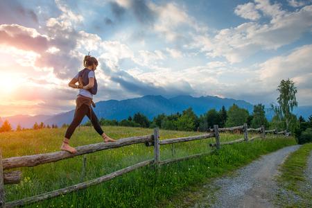 Muchacha ocasional que se relaja haciendo estiramientos y yoga solo en las montañas sobre una cerca en un prado hermoso de primavera.