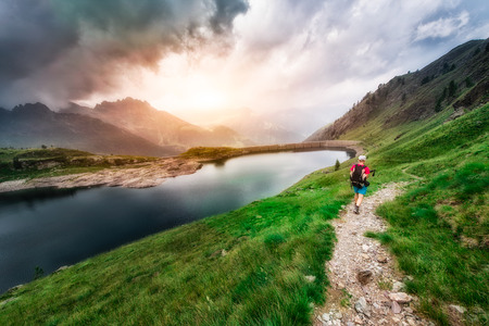 arrives: Woman hiker arrives at a mountain lake Stock Photo