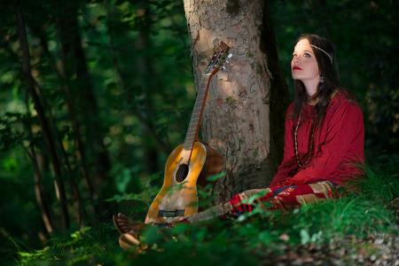 mujer hippie: Muchacha del Hippie con la guitarra en el bosque