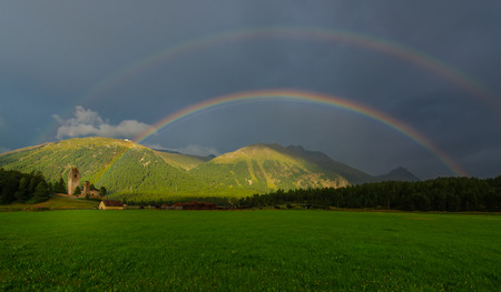 sunligh: Real full double rainbow in a mountain meadow Stock Photo