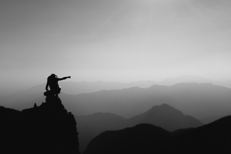 rocky peak: A climber looks and indicates mountains from a rocky peak Stock Photo