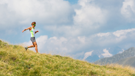 muscle women: Woman runs in the mountains in the meadow alone Stock Photo
