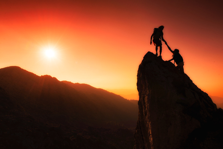 climber: Team van klimmers helpen om de top in teamwerk in een fantastische berglandschap bij zonsondergang veroveren Stockfoto