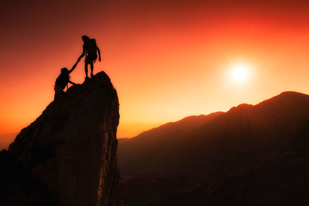 climbing: Personas de los escaladores ayudar a conquistar la cumbre en el trabajo en equipo en un fant�stico paisaje de monta�a al atardecer Foto de archivo